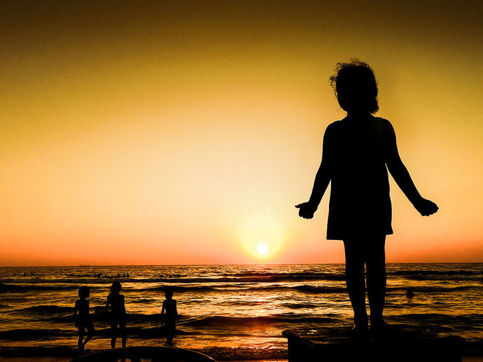 Popular Photos Water Sky Sea Real People Leisure Activity Lifestyles Men Horizon Nature Horizon Over Water Outdoors Sunset Silhouette Orange Color Beach Beauty In Nature Land Standing Scenics - Nature Women Sun