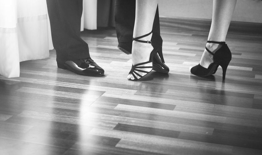 Low section of couple dancing on parquet floor