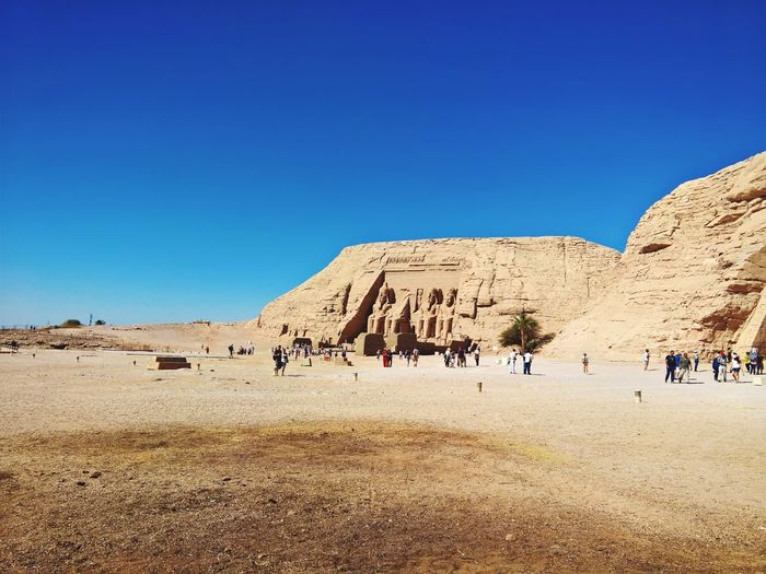 People at desert against clear blue sky