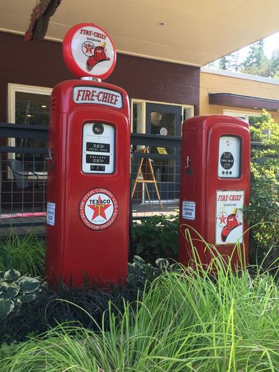 Yard Art Metal Art Gas Pumps Red Communication No People Telephone Text Grass Technology Architecture Obsolete Outdoors