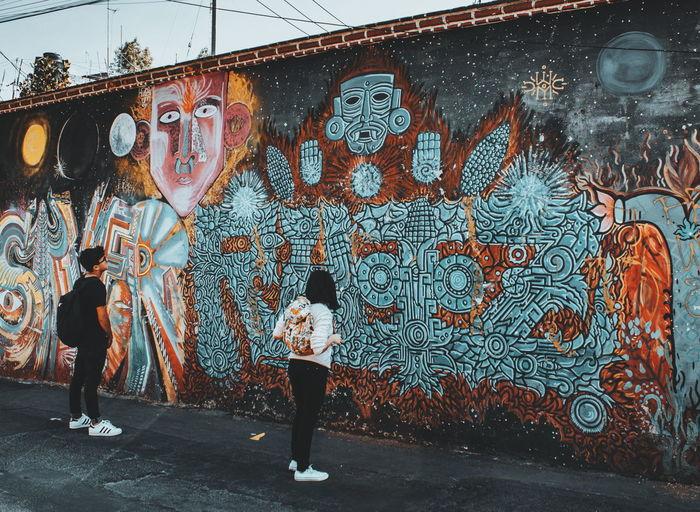 Full length of boy standing against graffiti wall