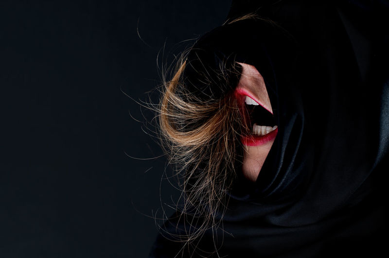 Close-Up Of Woman Screaming Against Black Background