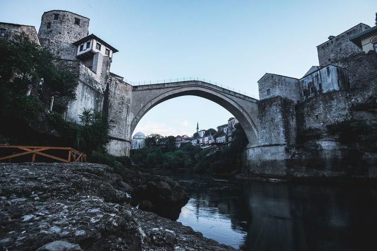Arch bridge over river amidst buildings against clear sky