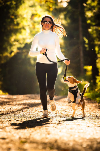 Woman wearing sunglasses walking dog on road