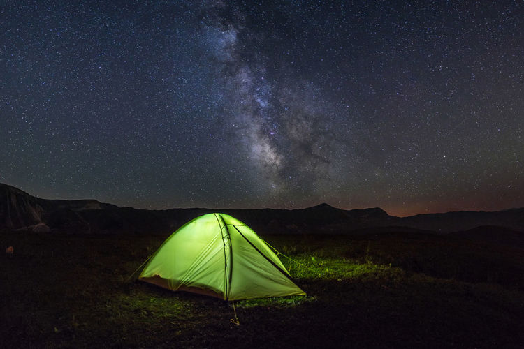 View of the tent and the milky way in the mountains
