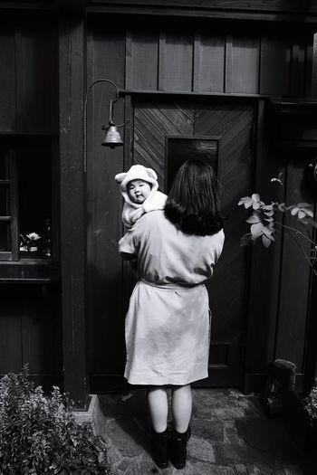 Rear view of woman standing against door
