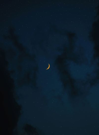 Low angle view of moon and stars  against sky at night