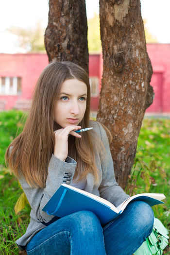 Woman With Book And Pen Sitting Against Tree In Park