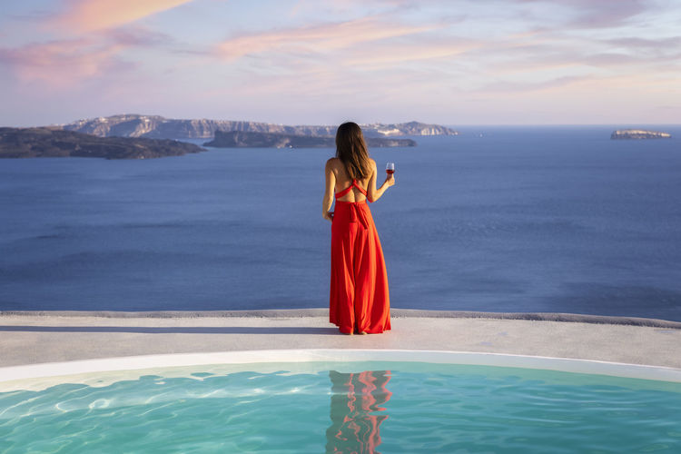 Woman standing in swimming pool by sea against sky