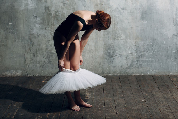 Full length of ballet dancer wearing tutu against gray wall