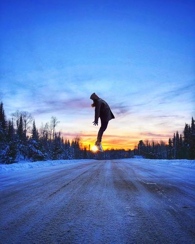 Silhouette man on road in city against sky during winter