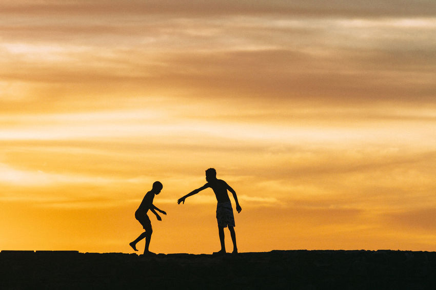Paint The Town Yellow Bonding Childhood Friendship Leisure Activity Playing Real People Silhouette Sky Sunset Togetherness Two People Walking Connected By Travel