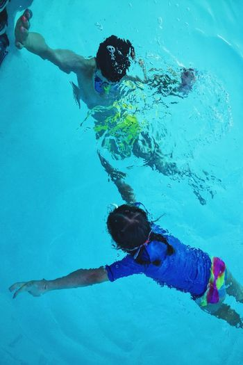High Angle View Man And Girl Swimming In Pool