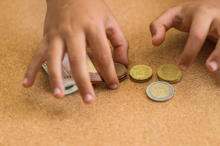 Close-up of hands counting coins and paper currency on table
