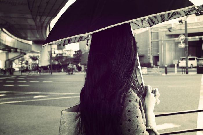 Woman under umbrella in city