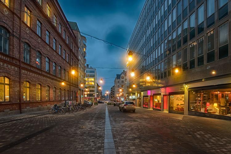 Illuminated street amidst buildings in city at dusk