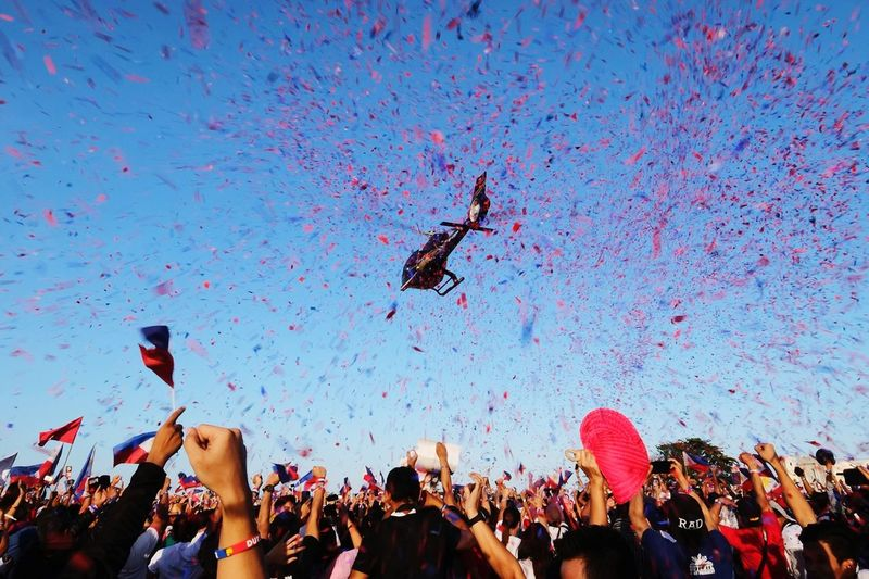 People with confetti falling from helicopter during festival