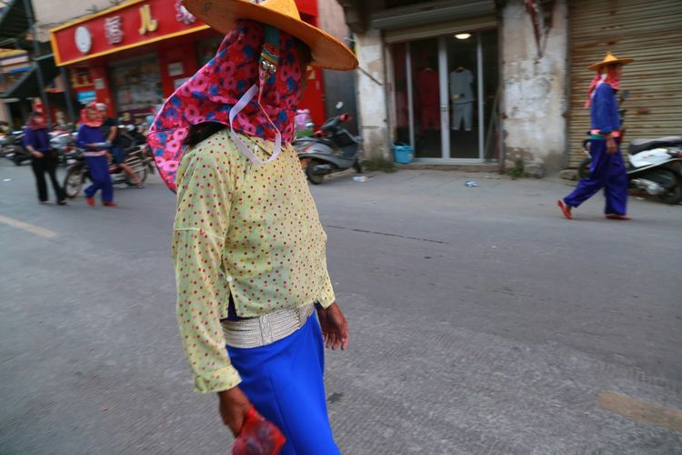 People wearing traditional clothing and walking on street