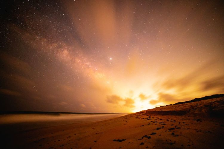 Scenic view of beach against sky at night with milly way