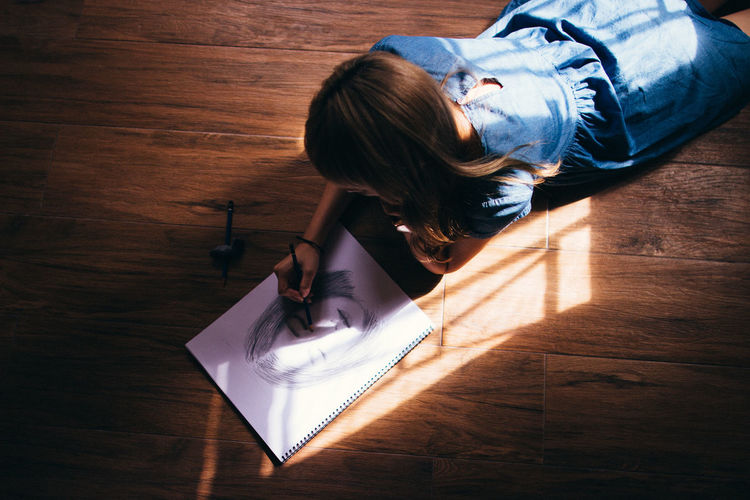 Woman Making Sketch While Lying On Hardwood Floor
