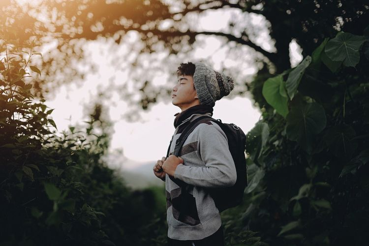 Close-up of young man standing in forest