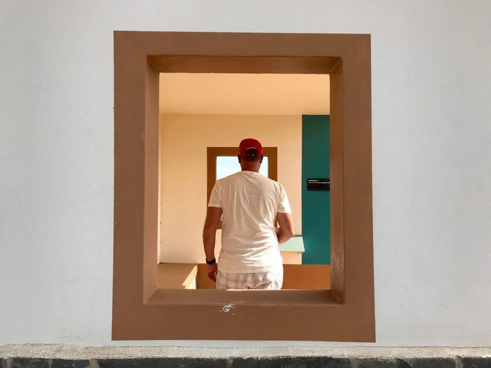 Rear view of man standing against door at home