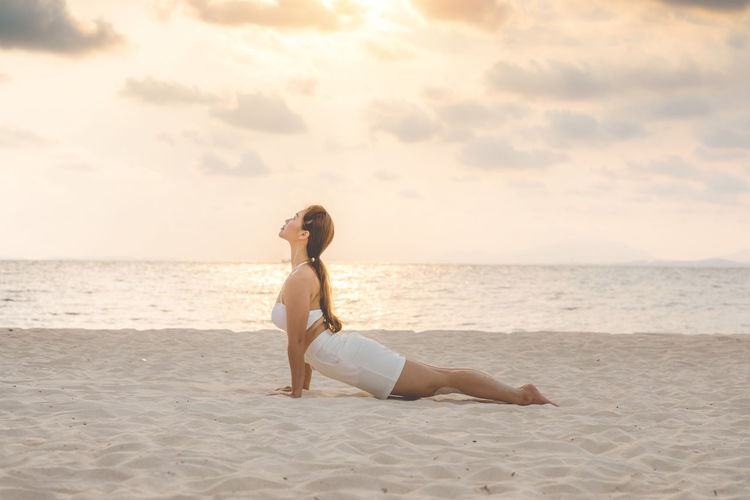 Full length of young woman doing yoga at beach