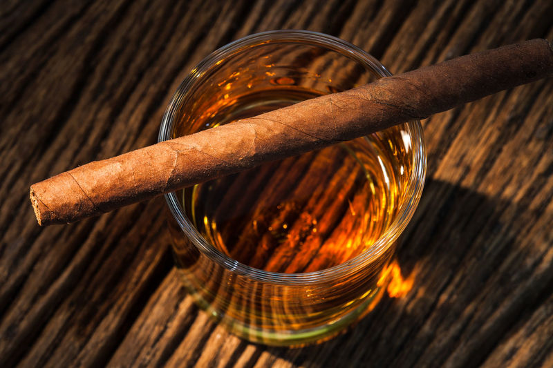 Close-up of cigar with whiskey glass on table