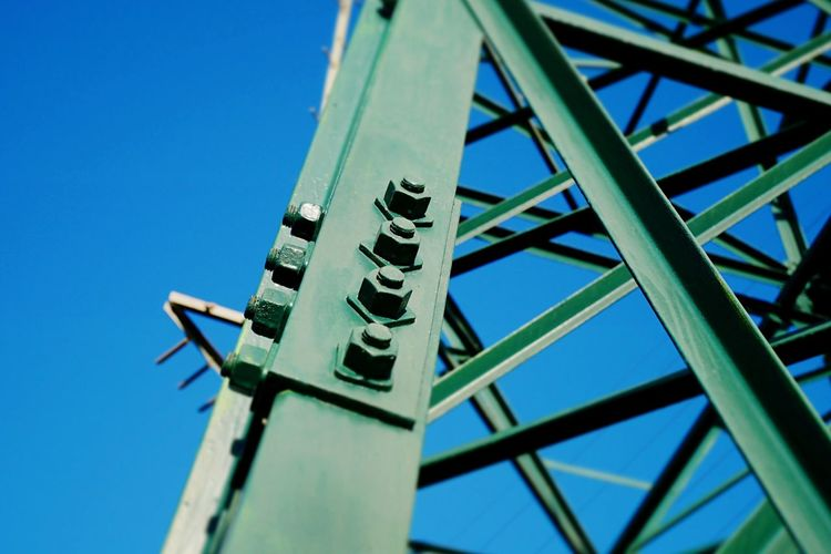 Pylon bolts. Low Angle View Electricity Pylon Bolts Blue Clear Sky Sky Day Close-up Technology Background Metal Green Color Outdoors Environment Built Structure Watt Connection Volt Safety Energy Environmental Rust Iron Tiltshift Tower