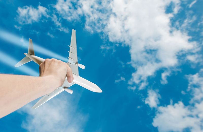 The Dream of Flight. Air Travel Idea Photo Concept with Airliner Airplane Model in a Hand. Business Flights. Dream Airplane Airplane Wing Blue Close-up Cloud - Sky Concept Day Flight Flying Human Body Part Human Hand One Person Outdoors Real People Sky