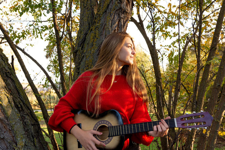 Smiling teenage girl playing guitar standing against tree