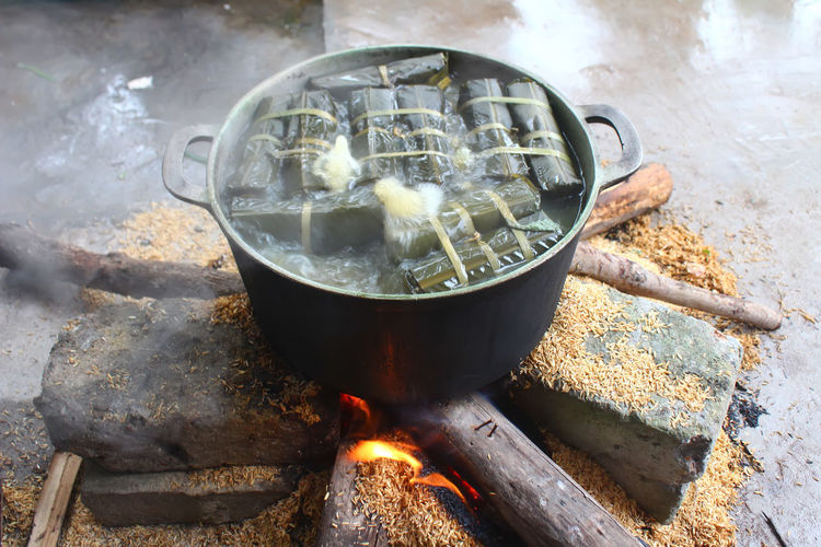 High angle view of food cooking in container on wood burning stove