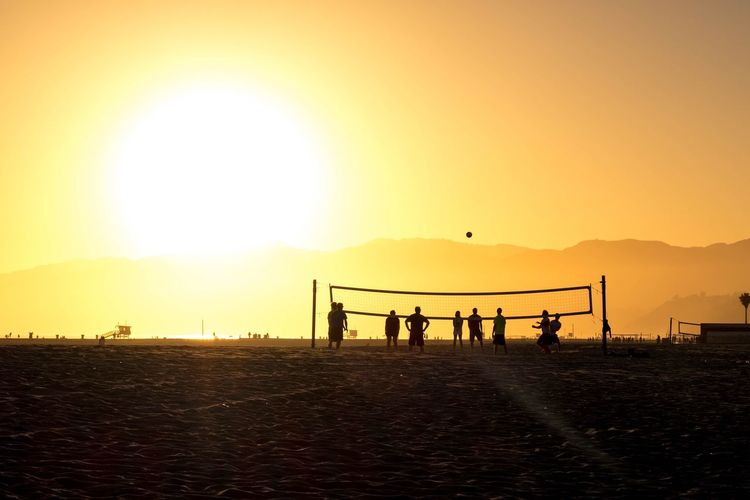 People Playing Volleyball At Beach Against Sky During Sunset