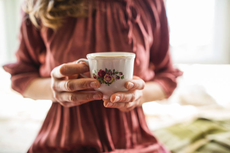 Midsection of woman drinking coffee in cup