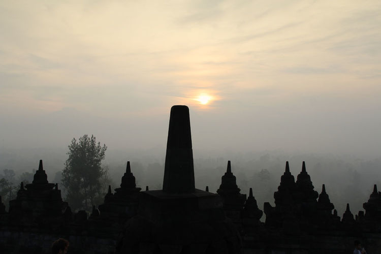 Silhouette Borobudur Temple with the mysteries forest surrounding during sunrise, Yogyakarta, Indonesia Ancient Borobudur Temple Java Yogyakarta Ancient Civilization Architecture Belief Buddhism Building Exterior Built Structure Dawn Fog Forest History Mount Merapi Nature No People Place Of Worship Religion Religious Architecture Silhouette Sky Spirituality Sunrise Sunset
