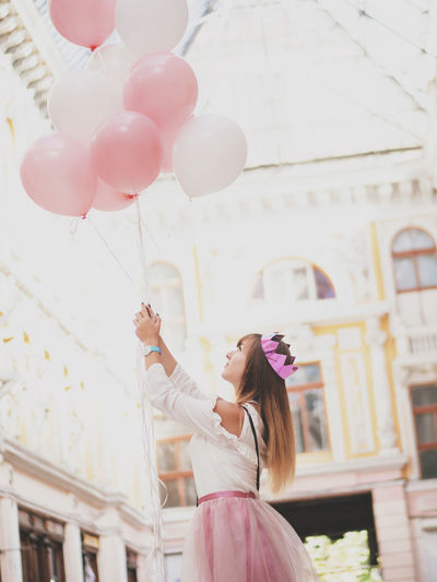 Side view of young woman holding pink balloons while standing against building