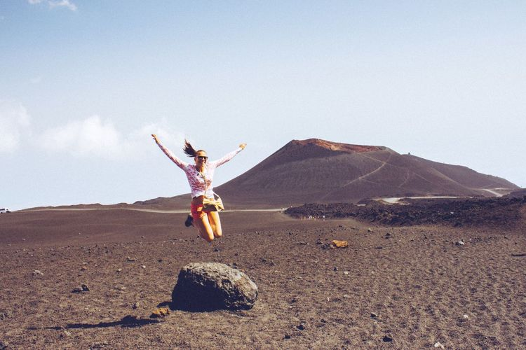 Full length of woman jumping over landscape with mt etna in background against sky