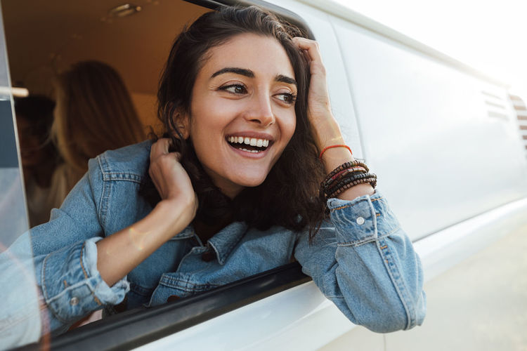 Portrait of smiling young woman sitting on car