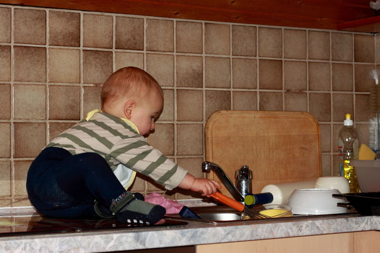 Side view of baby boy sitting by sink on kitchen counter