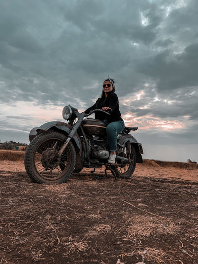 Full length of woman riding motorcycle on field