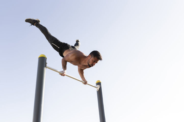Low angle view of man climbing on pole against clear sky