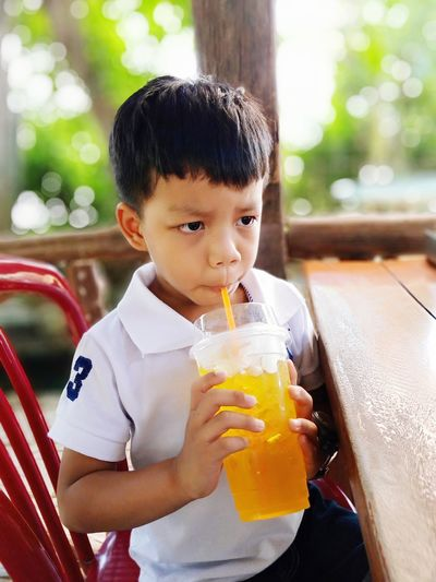 Boy drinking while looking away by table