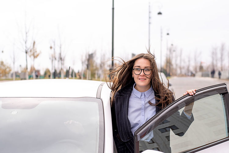 Portrait of young woman standing by car on road