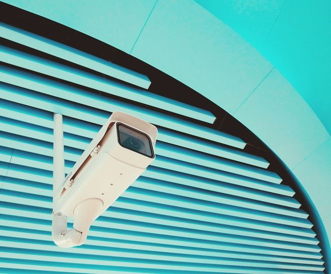 Low angle view of security camera hanging from turquoise ceiling