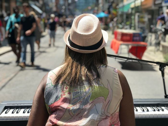 Rear view of woman performing on street in city