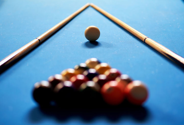 Close-up of pool balls and cues on table