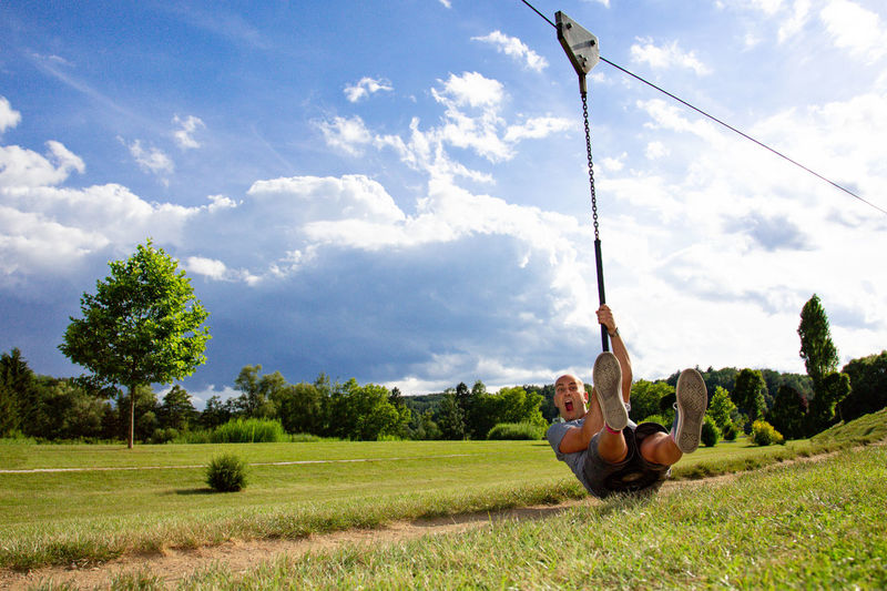 Full Length Of Man Screaming While Zip Lining Against Sky On Field