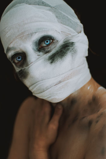 Portrait of young woman with bandage covering face against black background