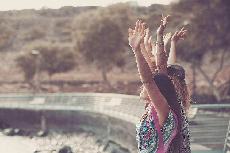 Female friends with arms raised standing at bridge