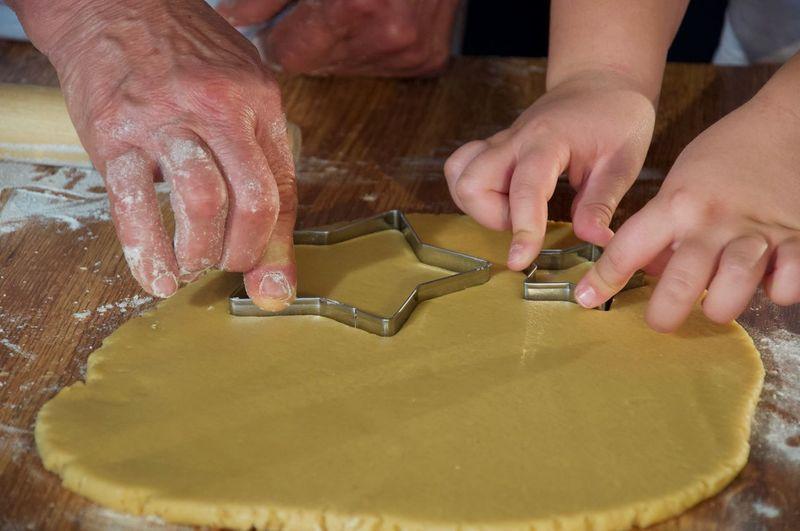 Cropped hands of people preparing cookies on table